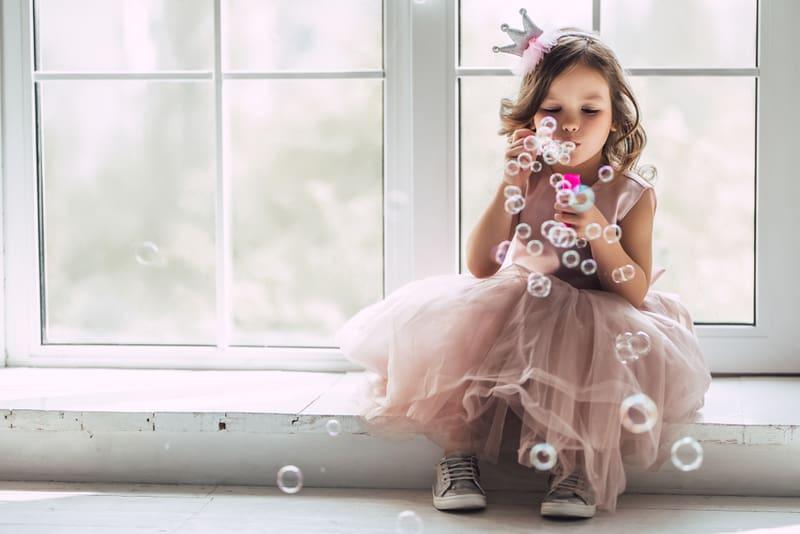 cute girl in beautiful dress is sitting near the window