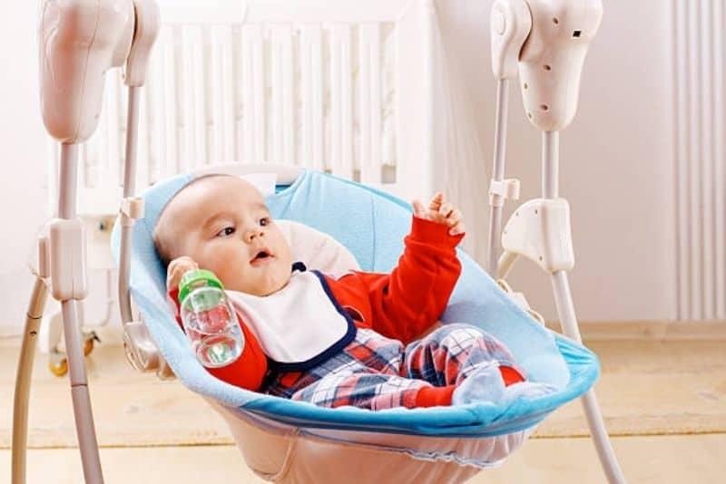 cute little baby boy in baby swing