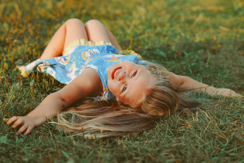 girl is lying on the green grass