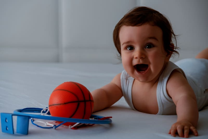happy baby boy playing with basketball on the bed