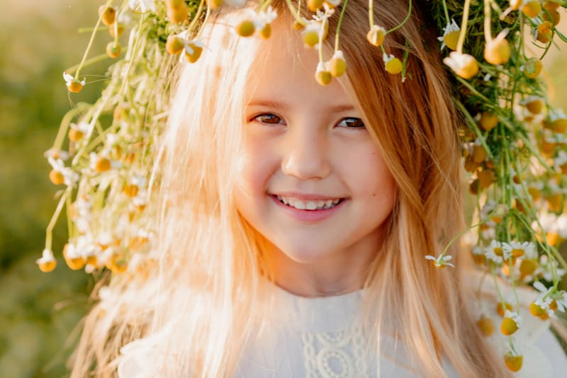 little blonde girl with a wreath of daisies on her head
