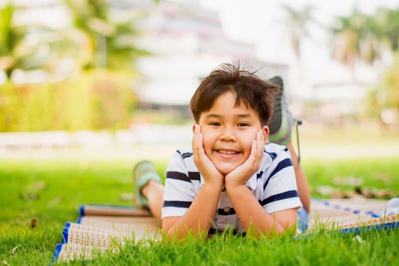 little boy lying in the park