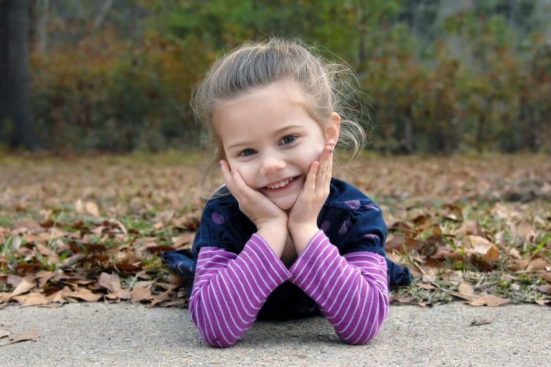 little girl laying on the Fall leaves
