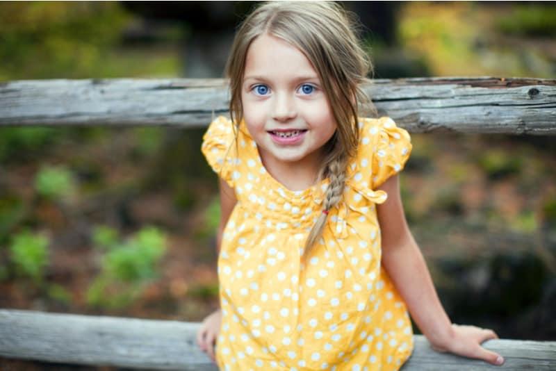 little girl wearing yellow dress outside
