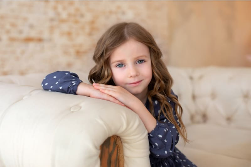 little girl sitting on a couch in living room