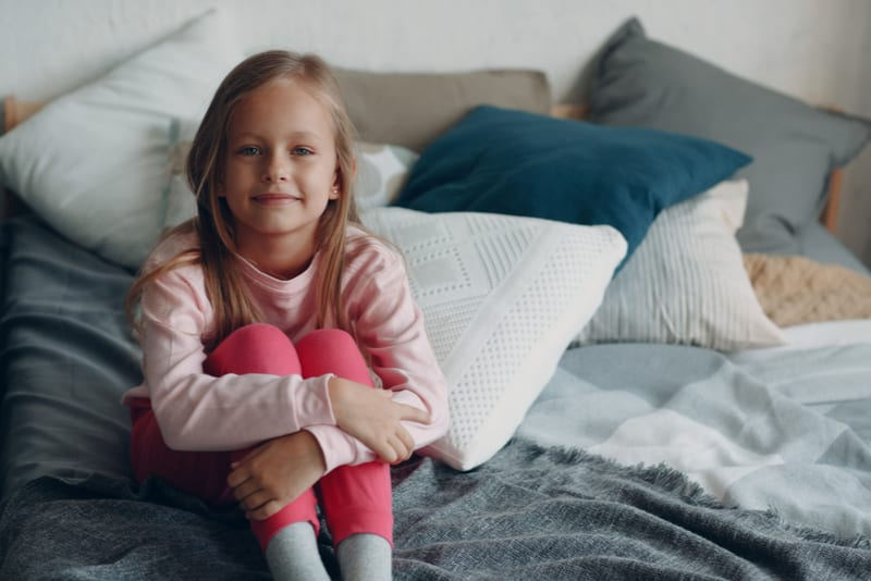 little girl sitting on bed