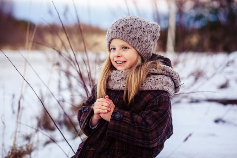 little girl wearing plaid coat and a cozy hat
