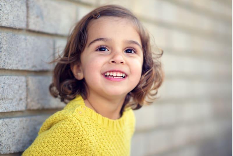 little girl wearing yellow sweater