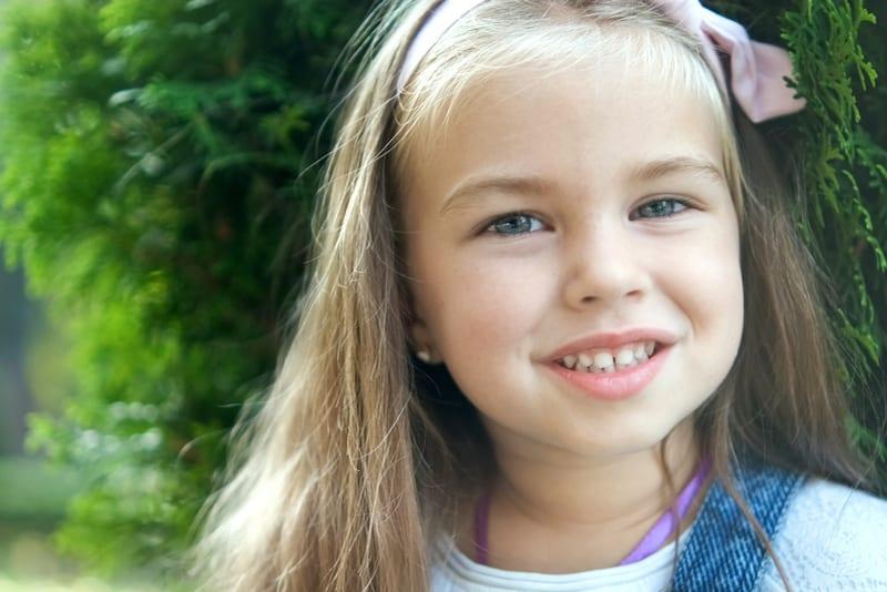 pretty child girl standing in summer park