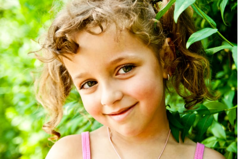 smiling little girl with curly hair outdoors