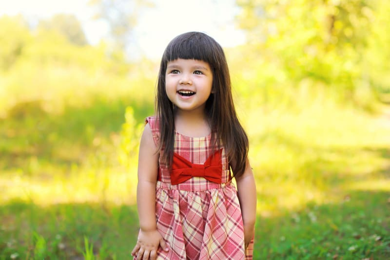 smiling little girl with long brown hair standing in a field
