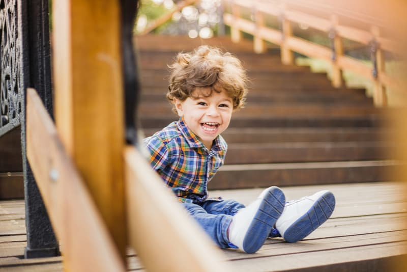toddler boy sitting and laughing joyfully