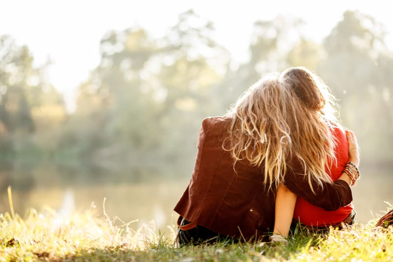 two young women sitting on grass hugging