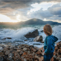 Little boy observing the storm on the beach