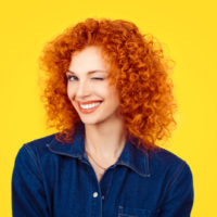 redhead woman with curly hair smiling and winking at the camera