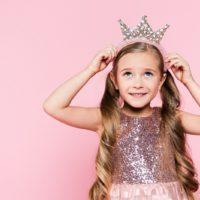 short little girl in a fancy dress puts a crown on her head