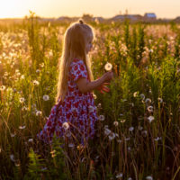 little girl with very long blonde straight hair in a floral dress