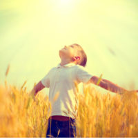 little boy spreading his arms wide open towards the sky on a sunny day