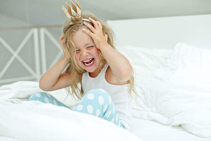 Adorable little girl awaked up in her bed with crown on head