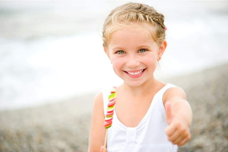 Adorable little girl holding candy