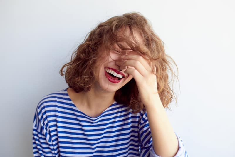 Laughing woman in marine shirt with curly hair