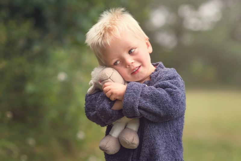 Little blond boy holding plush sheep in the park