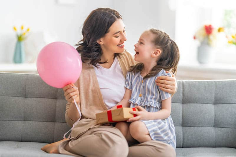 Mum and daughter smiling and holding baloon