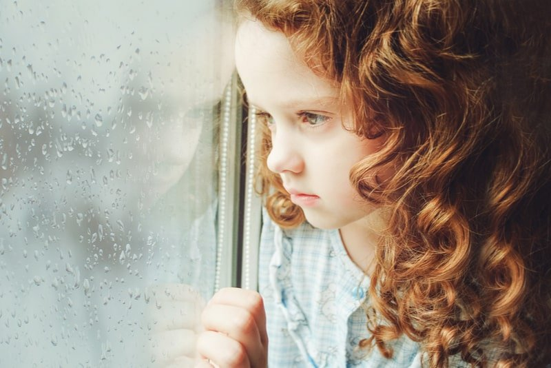 Sad child girl looking out the window