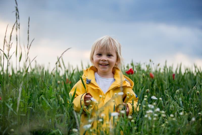Sweet blond boy playing in poppy field before storm