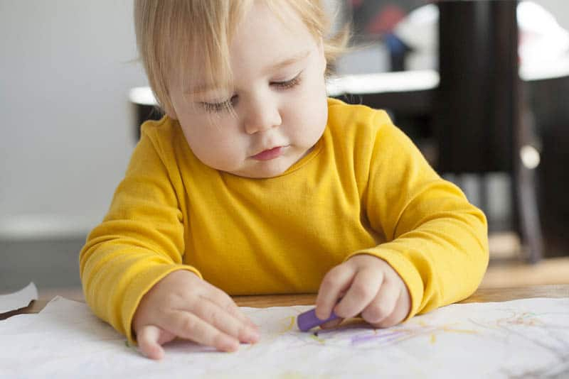 adorable baby girl sitting by the table and drawing on white paper