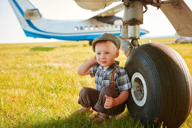 adorable little boy sitting near the aeroplane