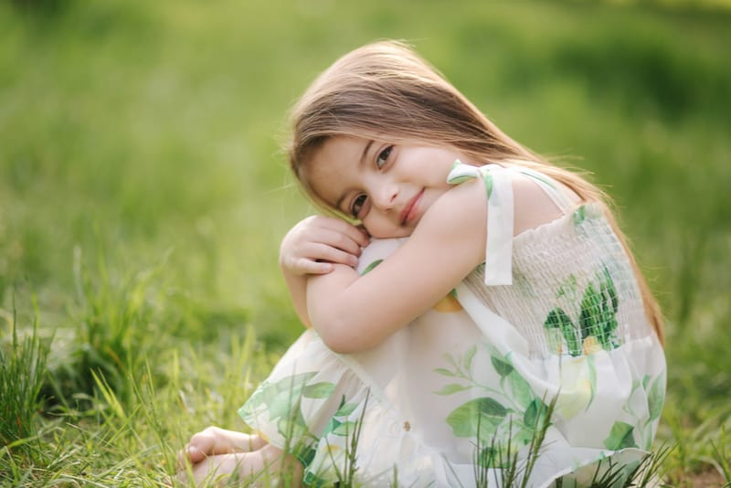 adorable little girl sits barefoot on the grass in the park