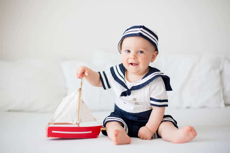 baby boy wearing a sailor clothes and playing with wooden boat on the floor