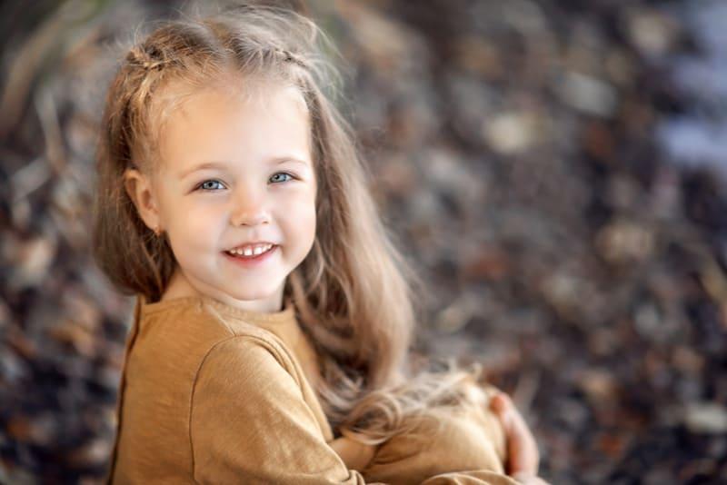 beautiful little girl sitting on a rocky beach