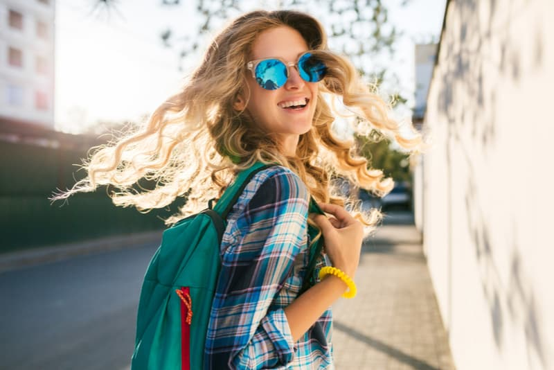 blond girl walking on street with backpack