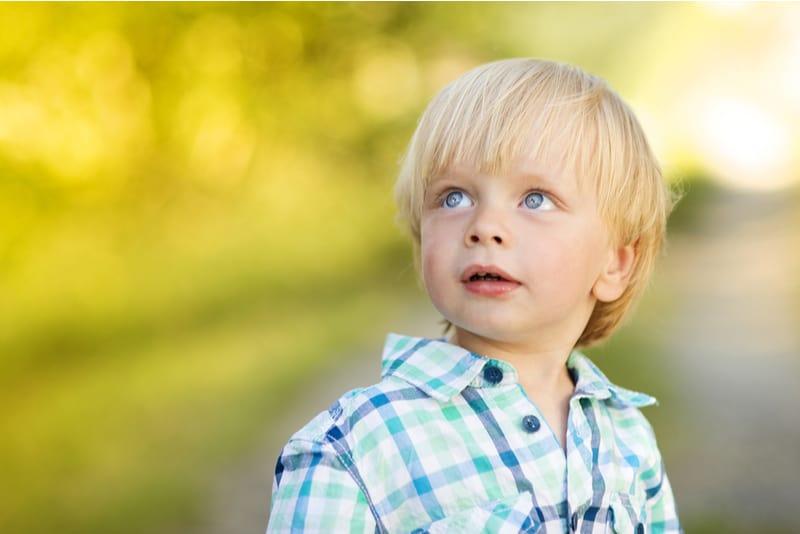 blonde little boy posing outside