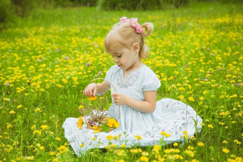 blonde little girl playing with the flowers