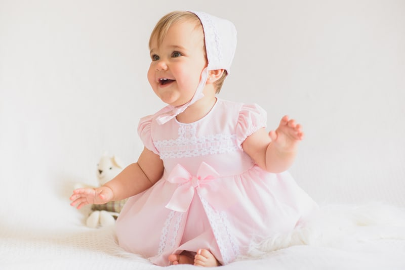 cute baby girl wearing pink dress and a hat