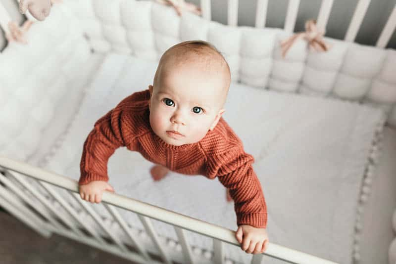 cute baby girl wearing sweater standing in the crib and looking up