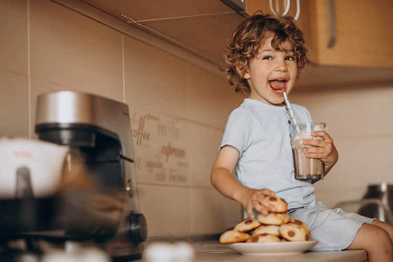 cute little boy sitting on the kitchen with plate of cookies and a chocolate milk