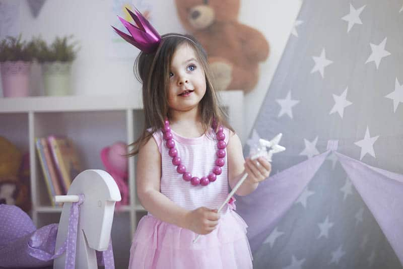 cute little girl playing a princess role at home with crown on head