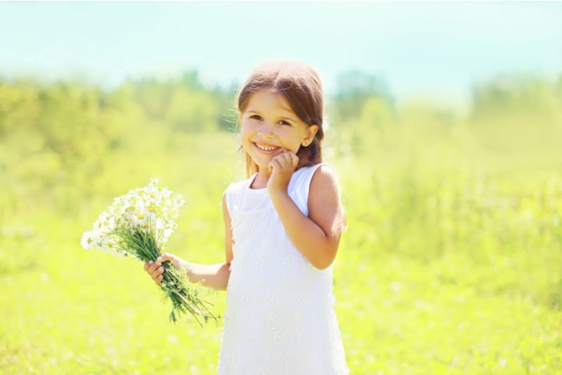 happy smiling little girl with flowers