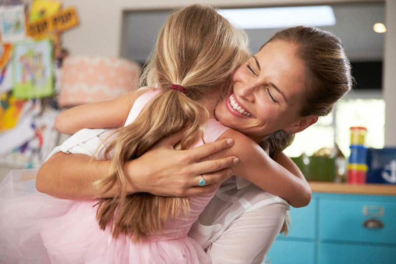 happy young mother hugging her cute daughter