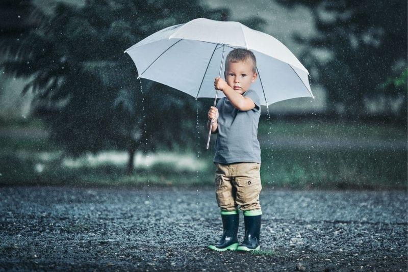 little boy outdoors holding umbrella