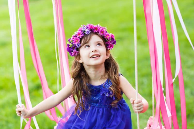 little girl wearing blue dress at park
