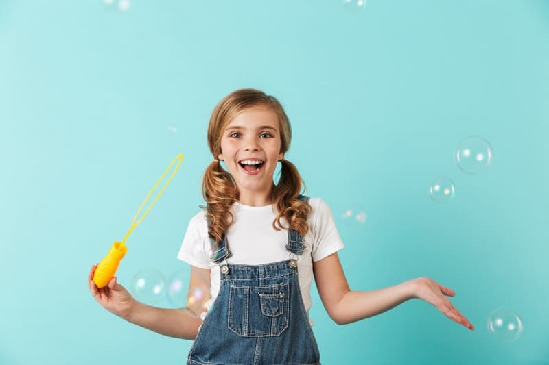 little girl with pigtails blowing bubbles and laughing