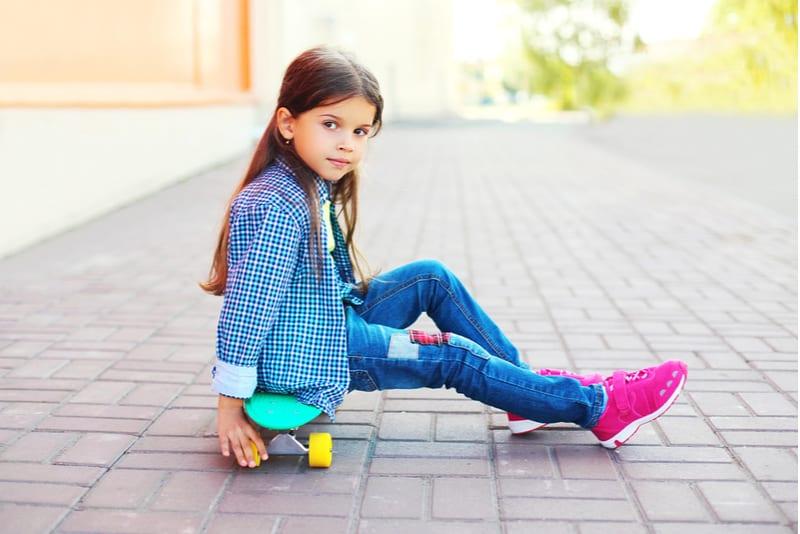 little girl child sitting on skateboard