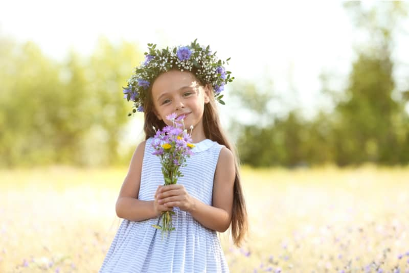 little girl holding beautiful wreath with bouquet of wildflowers