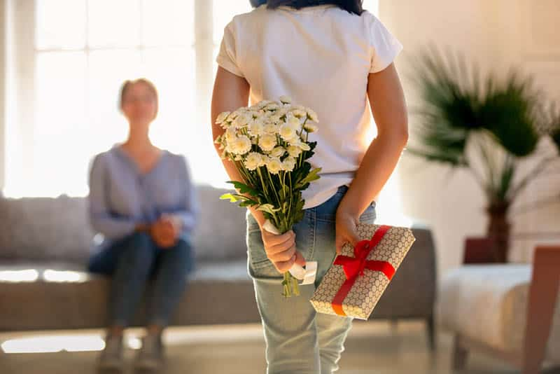 little girl holding gift and flowers as a surprise for mother