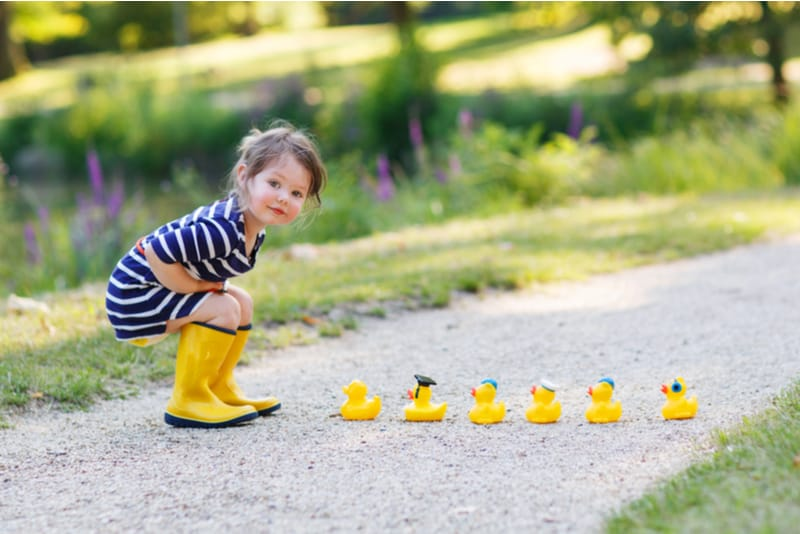 little girl playing with yellow rubber ducks